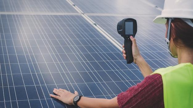 Vrouweningenieur die thermische imager gebruiken om temperatuurhitte van zonnepaneel te controleren