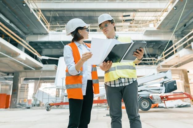 Vrouweningenieur en man bouwer bij bouwwerf