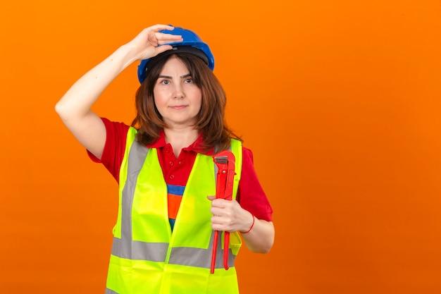 Vrouweningenieur in bouwvest en de holding van de veiligheidshelm met regelbare moersleutel wat betreft helm die zeker over geïsoleerde oranje muur kijken