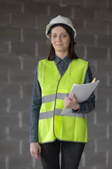 Vrouweningenieur in een witte helm en veiligheidsvest de ingenieur op de bouwwerf