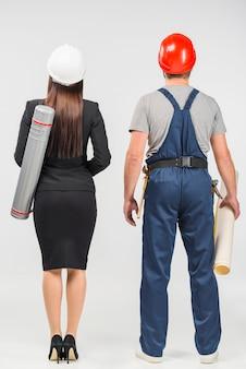 Vrouweningenieur in kostuum die zich met bouwer bevinden