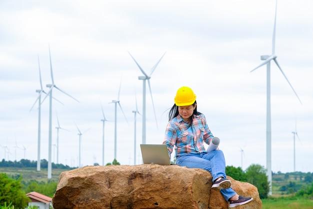 Vrouweningenieur of architect met witte veiligheidshoed en windturbines op achtergrond