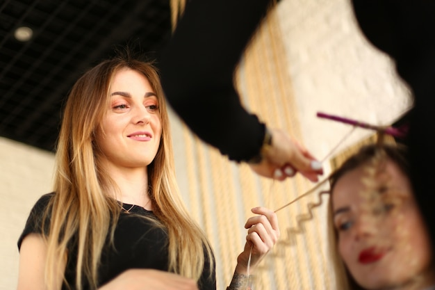 Vrouwenkapper die krullend kapsel bekijken