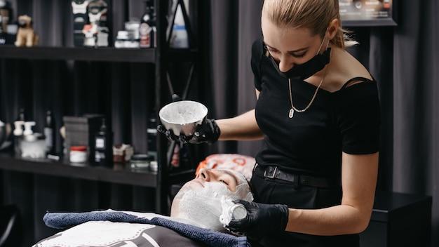 Vrouwenkapper die scheerschuim toepassen alvorens met een scheermes te scheren.