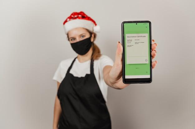 Vrouwenkelner in kerstmuts en beschermend masker houdt smartphone vast met covid-vaccinatiecertificaat