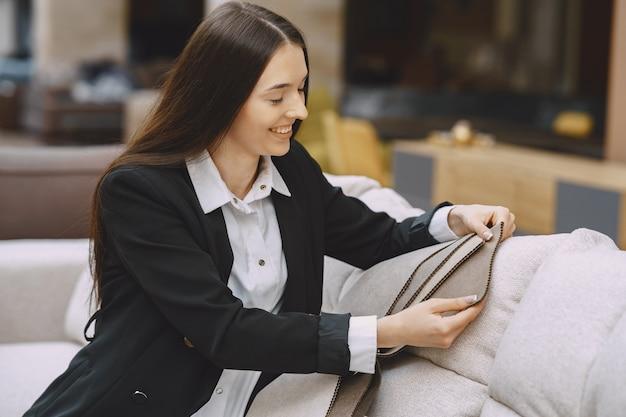 Vrouwenklant die mooie stof in gordijnwinkel zoeken