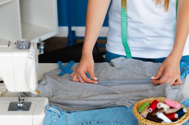 Vrouwenkleermaker die metingen met het meten van band in haar bureau maken