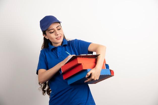 Vrouwenkoerier die in klembord schrijft en kartonnen pizza vasthoudt