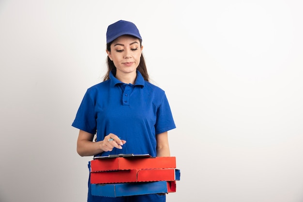 Vrouwenkoerier die op karton van pizza en klembord kijkt