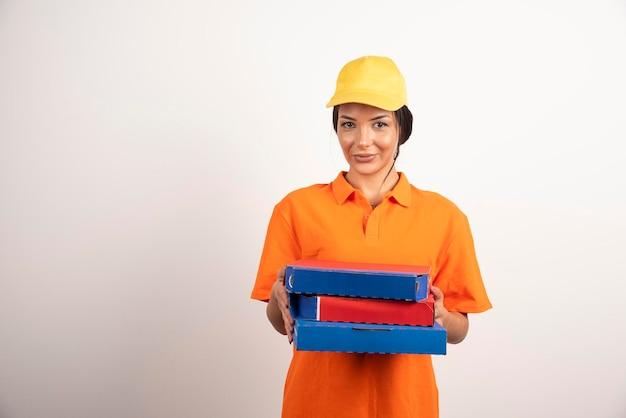 Vrouwenkoerier in uniform die pizza's op witte muur weggeeft.