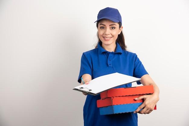 Vrouwenkoerier met karton van pizza die klembord geeft. hoge kwaliteit foto