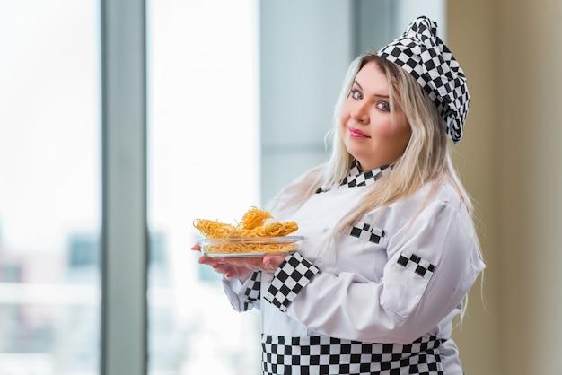 Vrouwenkok die in de heldere keuken werken