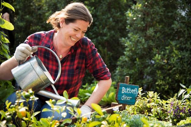 Vrouwenlandbouwer die bij platteland tuinieren