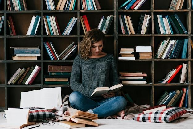 Vrouwenlezing op vloer dichtbij boekenrek