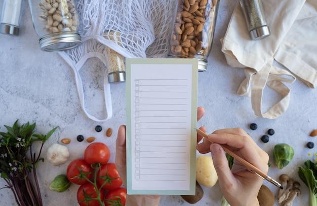 Vrouwenlijst op de notitie voor veganistisch gezond eten en een levensstijl zonder afval. plastic gratis boodschappen. bovenaanzicht. plat liggen