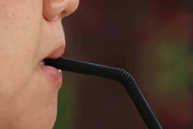 Vrouwenlippen die of door zwarte plastic stro zuigen drinken.