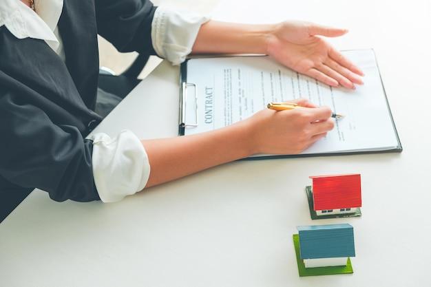 Vrouwenmakelaar die toont waar te ondertekenen op document voor het contract van de koophuis