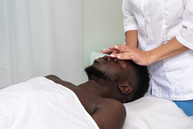 Vrouwenmasseur die een gezichts- en hoofdmassage doet aan zwarte man