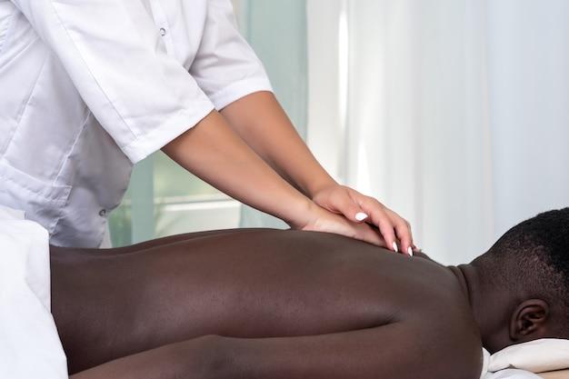 Vrouwenmasseuse die massage van ruggebied aan zwarte man doet