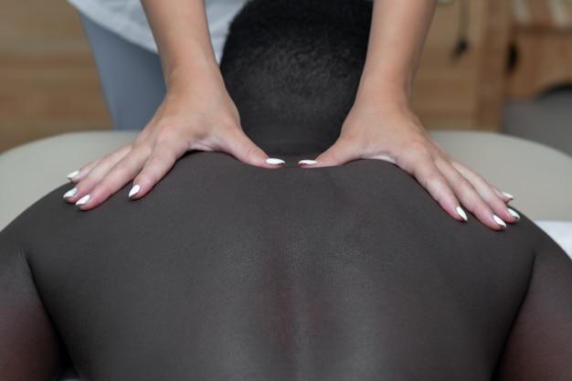 Vrouwenmasseuse die massage van schoudergebied doet aan zwarte man
