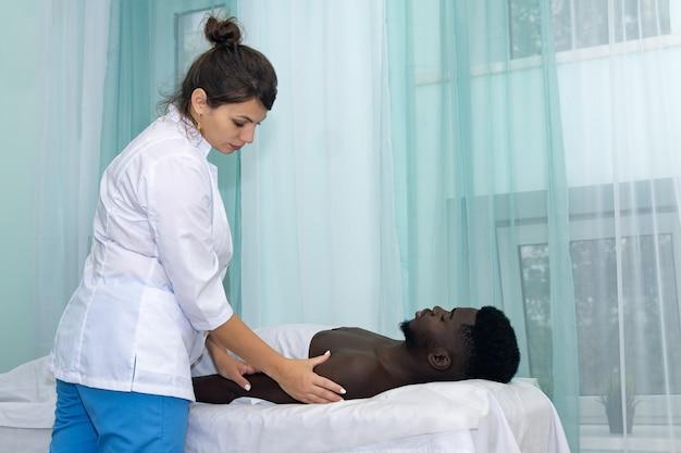 Vrouwenmasseuse die massage van schoudergebied van hand aan zwarte man doet
