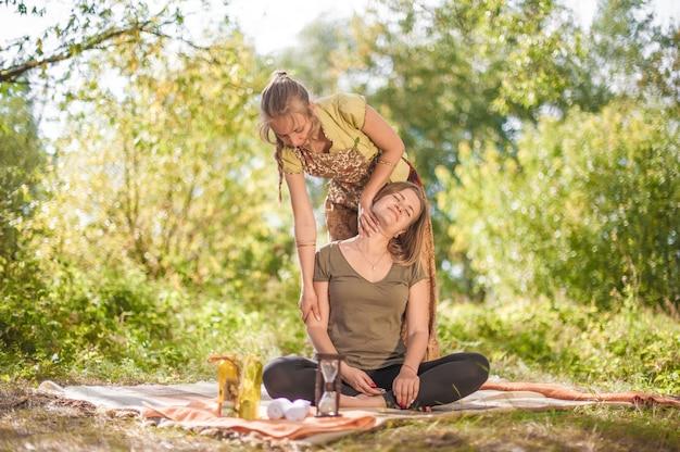 Vrouwenmasseuse past haar massagevaardigheden toe op haar cliënt op het gras van het bos.