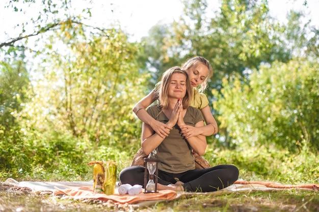 Vrouwenmasseuse voert adequaat een geweldige massage uit in de rustige buitenlucht.