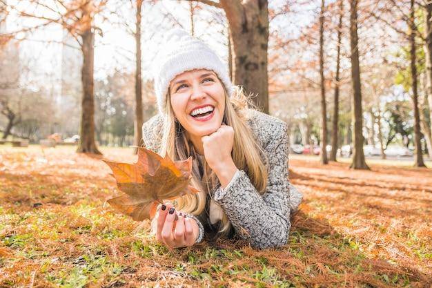 Vrouwenmodel die en op de herfstgrond glimlachen leggen