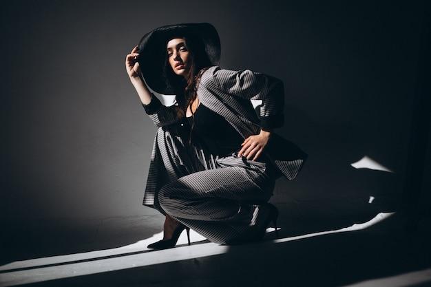 Vrouwenmodel in een pak die een hoed dragen