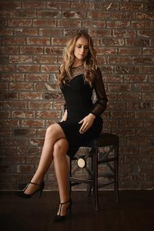Vrouwenmodel met perfect lichaam en lange sexy benen in een korte zwarte jurk zit op een stoel voor een bakstenen muur
