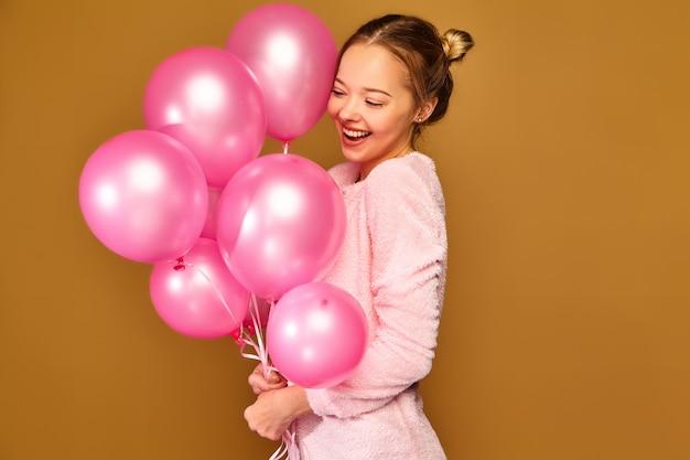 Vrouwenmodel met roze luchtballons op gouden muur