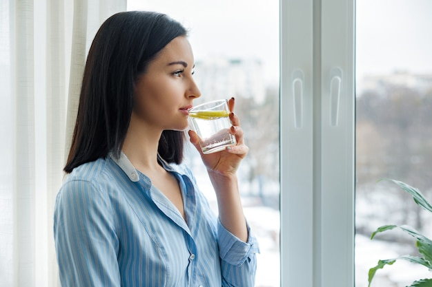 Vrouwenochtend dichtbij het venster drinkwater met citroen