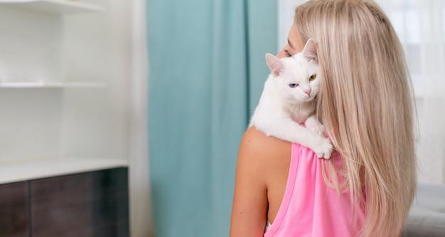 Vrouwenomhelzing met haar witte kat met heterochronia thuis