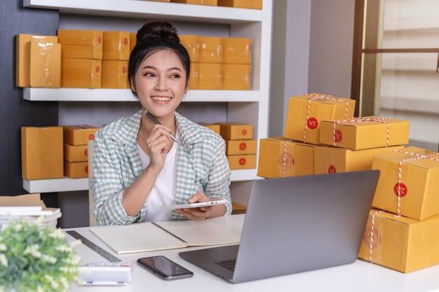 Vrouwenondernemer die en tablet en pakketdoos, online zaken denken gebruiken