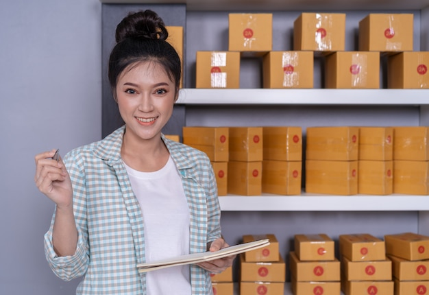 Vrouwenondernemer met pakketdozen in haar eigen baan die online zaken thuis winkelt