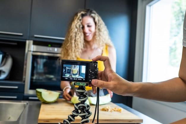 Vrouwenopname met een camera zoals een meloensnijder in een keuken