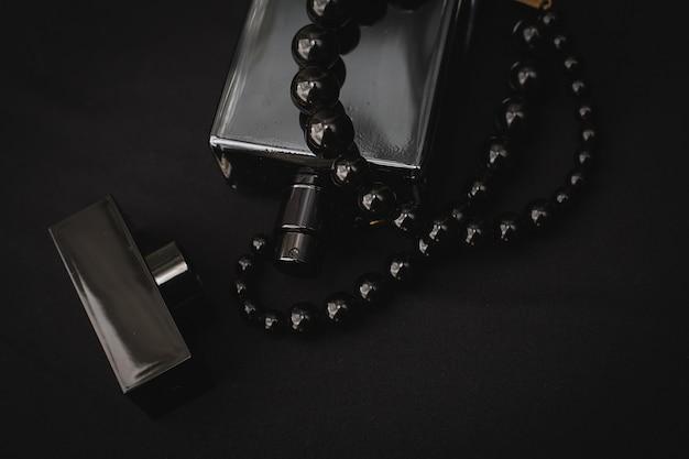 Vrouwenparfum in mooie fles en kralen, op zwarte achtergrond
