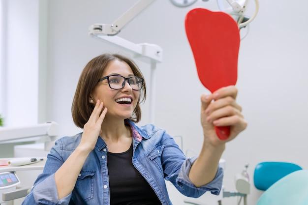 Vrouwenpatiënt die in de spiegel de tanden bekijken