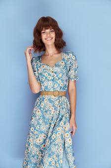 Vrouwenportret dat en een bloemkleding glimlacht draagt