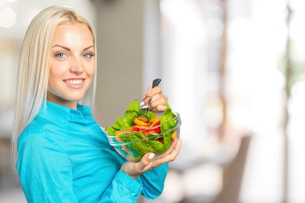 Vrouwenportret die groene salade met tomaten eten