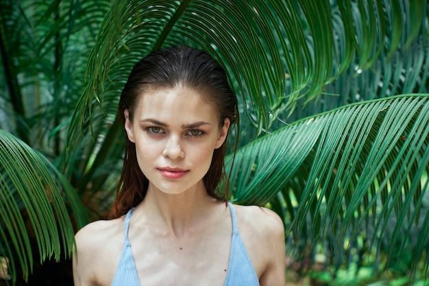 Vrouwenportret, groene bladeren van palmbomen, mooi gezicht