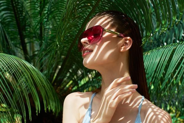 Vrouwenportret in glazen, groene bladeren van palmen, mooi gezicht