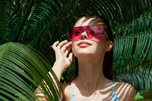 Vrouwenportret in glazen op groene bladeren van palmen, mooi gezicht