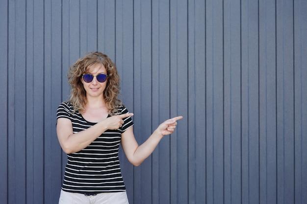 Vrouwenportret in zonnebril op blauw gestreepte muur op de achtergrond