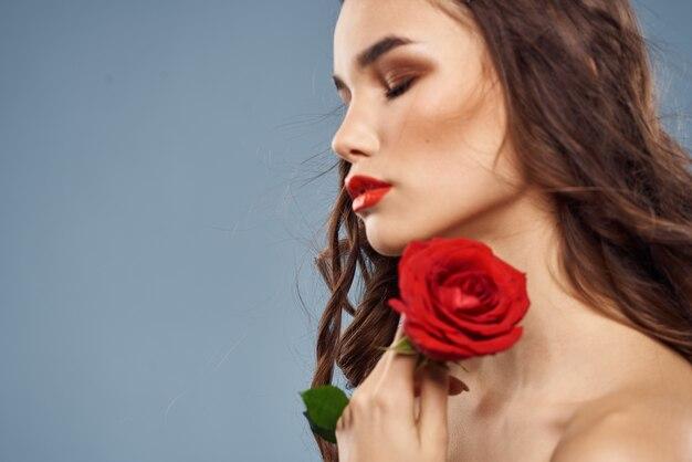 Vrouwenportret met rode roos in de buurt van het gezicht op grijze muur en make-up krullend haar.