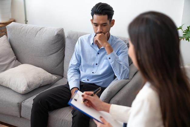 Vrouwenpsychiater die informatie van aziatische jonge man patiënt schrijven terwijl het spreken over zijn ziekte.