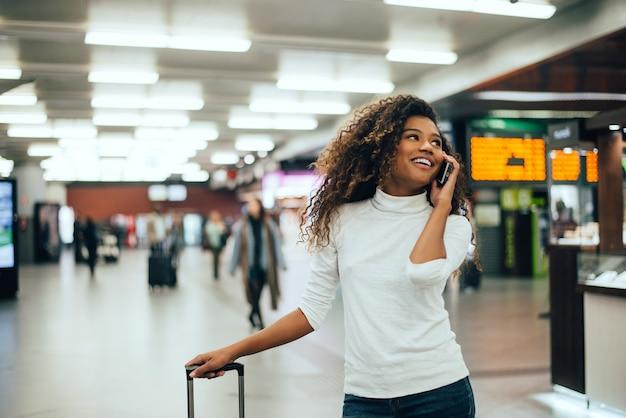 Vrouwenreiziger die op telefoon in de luchthaven eindgang met de bagage van de reiszak spreken.