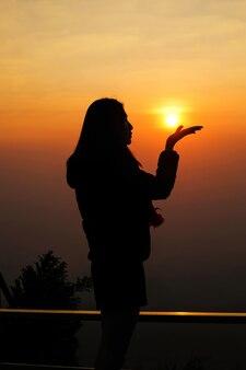 Vrouwenreiziger die zich bovenop de berg bevinden en voor mening van aard genieten wanneer de zonsondergang.