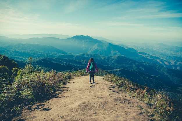 Vrouwenreiziger met rugzak bij bergenmening terwijl trekking op doi inthanon