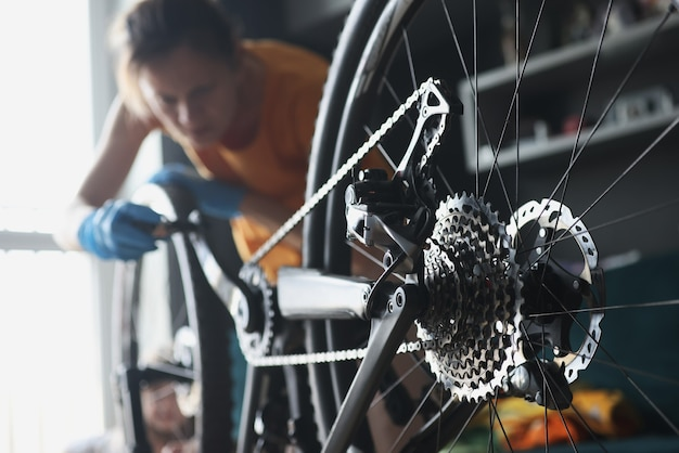 Vrouwenreparateur die in rubberhandschoenen fiets met hulpmiddelenclose-up herstellen